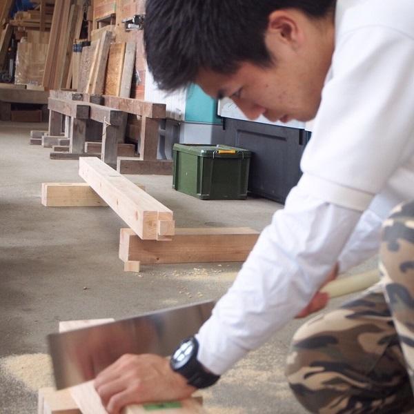 ノコギリで木材を加工しています。
