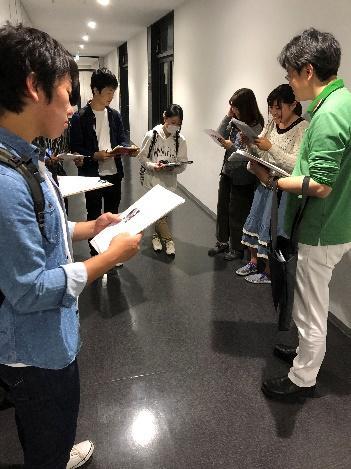 田中先生が学部生に研究室について説明している様子