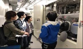 M1川瀬さんがMOCVD装置について説明している様子。