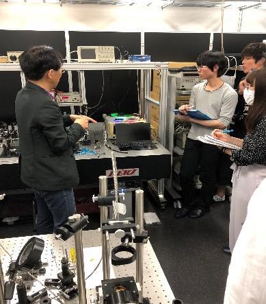 宮嶋先生が学部生に光ファイバーについて説明している様子