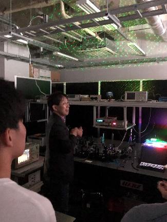宮嶋先生が学部生にレーザーの応用について説明している様子