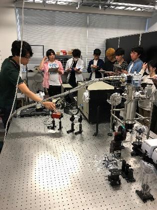 今井先生が学部生に実験装置について説明している様子