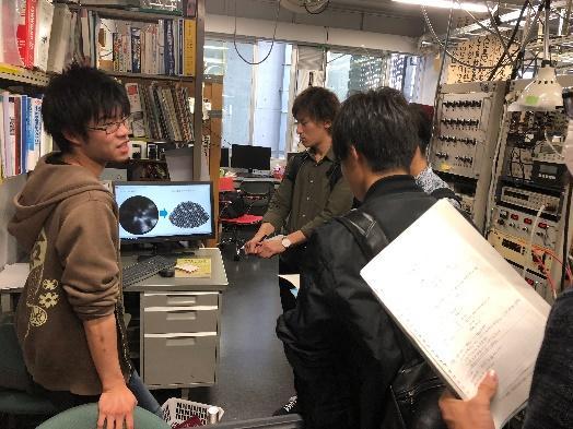 大学院生が学部生に測定装置の原理を説明している様子