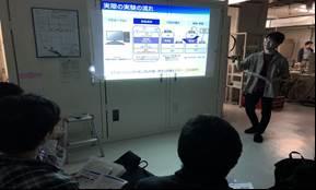 B4田中さんが研究室における実験の流れについて説明している。