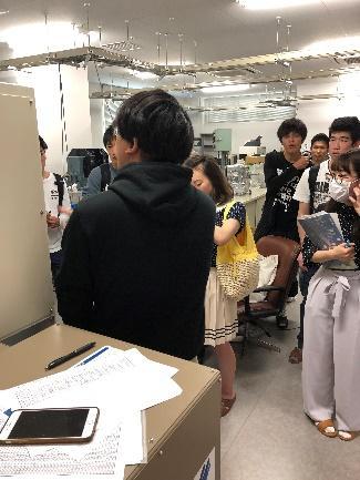大学院生が学部生に実験装置について説明している様子