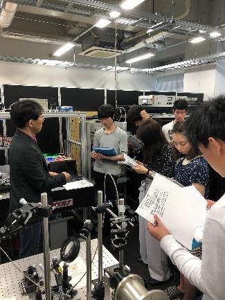 宮嶋先生に研究室での研究内容について説明している様子