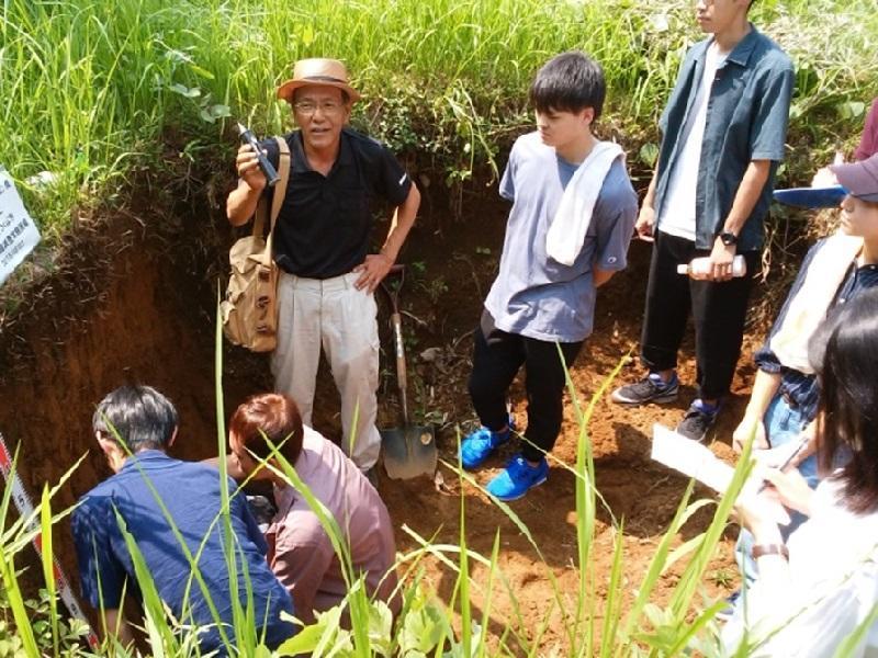 つくば台地の黒ボク土断面に触れながら土壌の成り立ちの解説を受ける学生たち。