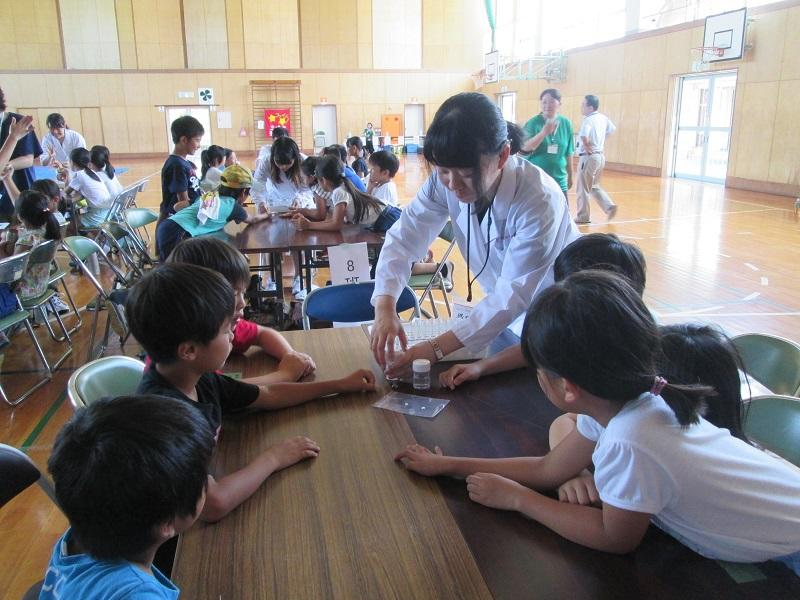 おくすり110番メンバーが補助し、児童が体験実験を行っている様子