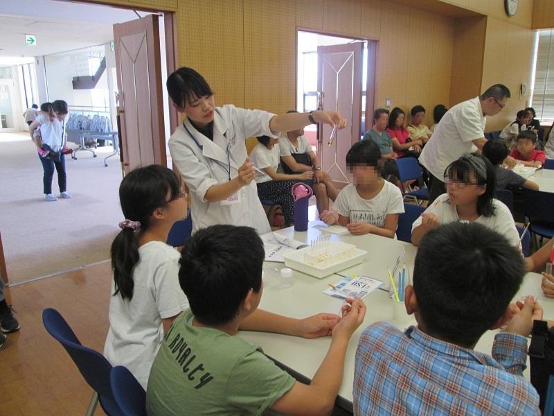 一宮薬剤師会の薬剤師が児童に体験実験を説明し、おくすり110番メンバーが体験実験を補助している様子