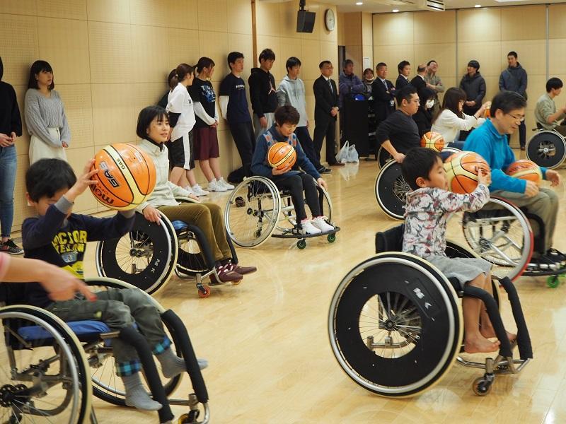 参加者には地域の小学生も多数見られ、不安定な車椅子上でボールを突く難しさを体験しています