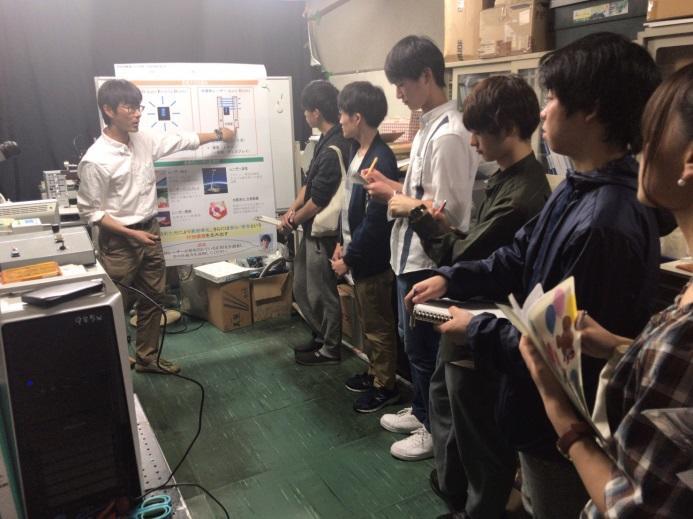 ポスターを使って、LEDと半導体レーザの違いや半導体レーザの応用先を竹内哲也先生が解説している様子です。