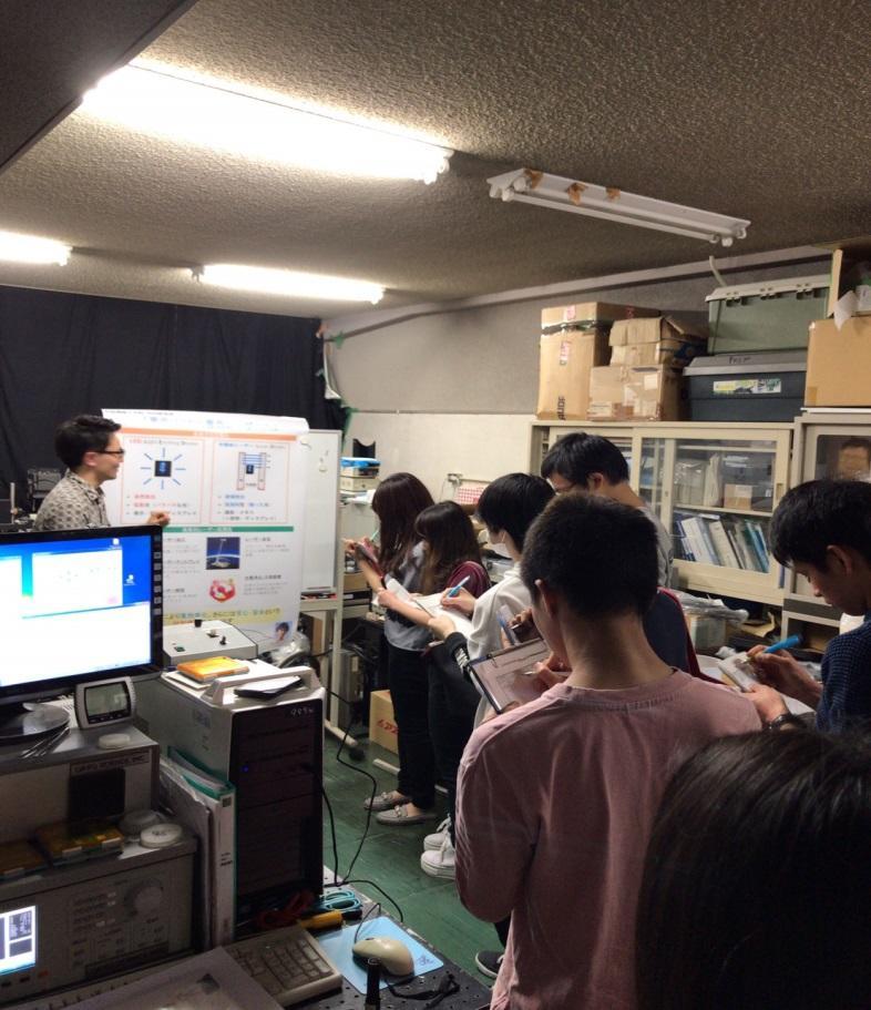 ポスターを使って、LEDと半導体レーザの違いや半導体レーザの応用先を竹内研究室の学生が解説している様子です。