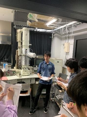この写真は田中研究室のゼミ長である辻君が透過電子顕微鏡(TEM)を用いて説明している様子です。材料の2年生はまだ実験を行っておらず、TEMについて全く知らなかったため、丁寧に使い方やTEMによって見られるものを説明していました。
