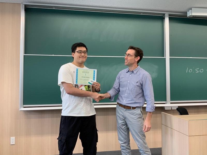 固い握手を交わす加藤さんとウィッキン先生
