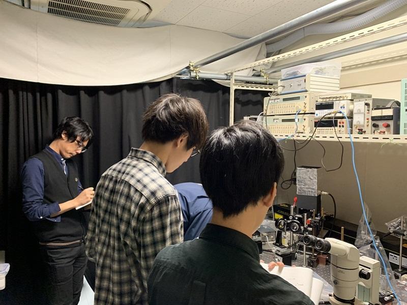 励起用レーザーを試料に照射するためにミラーの位置を調節しているのを見学している写真。