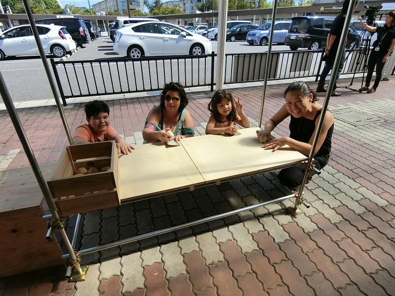 学生たち指導による、木片を削るワークショップに参加する外国人たち。
