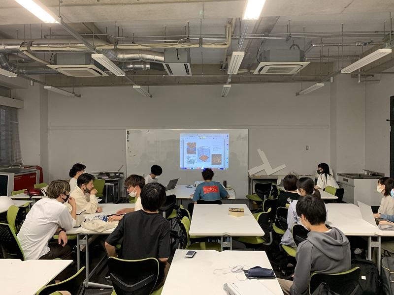 演習室で、各グループがプレゼンしながら、検討を進める。