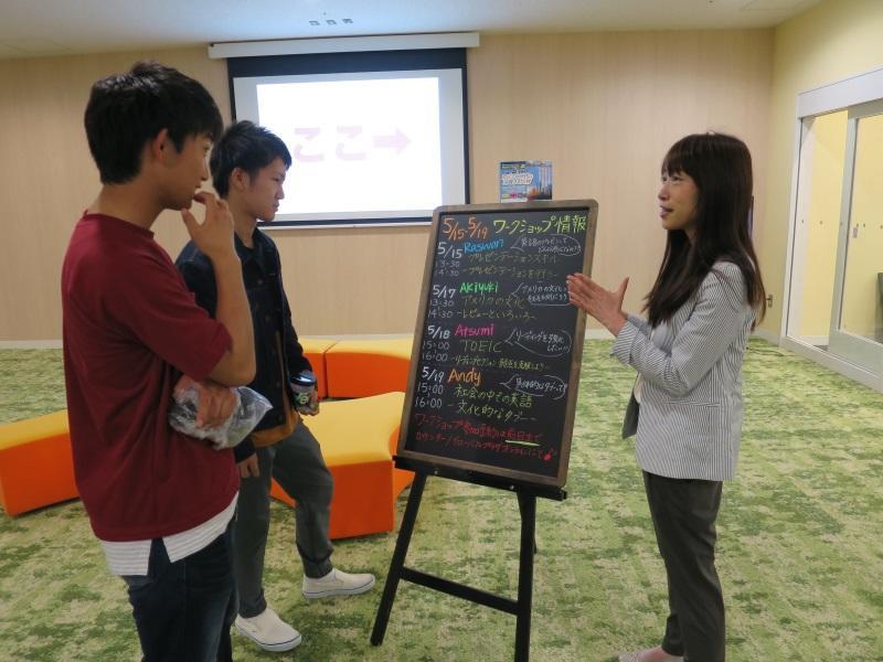 ワークショップ情報の看板と、参加を呼び掛ける山口さん(右)=天白キャンパスのグローバルプラザで