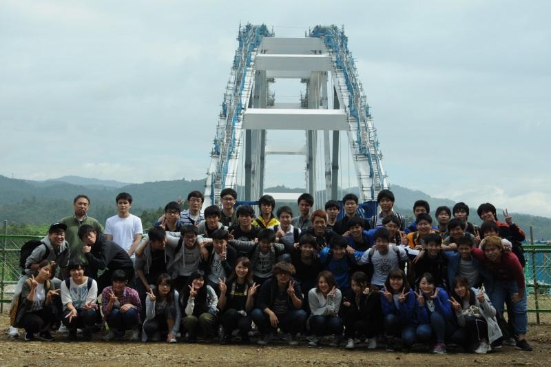 建設中の鶴亀大橋をバックに記念写真に納まる参加者たち=宮城県気仙沼市大島で