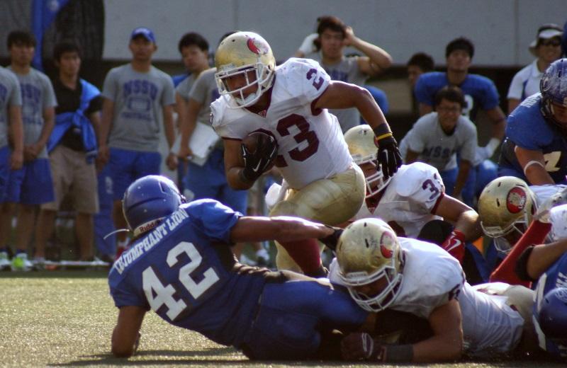 日本体育大学(青のユニホーム)の守りを突破するアメフト部員=東京都の同大グラウンドで