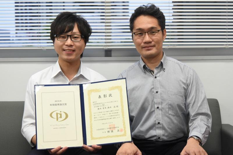 表彰状を手にする鈴木さん(左)と鈴木教授