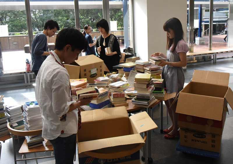 集まった本を整理して段ボール箱に詰めるBook-aidのメンバー