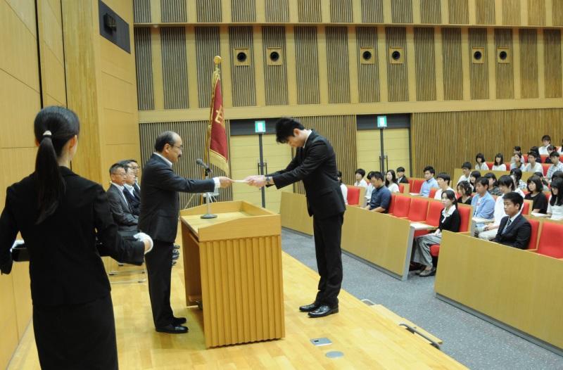 吉久光一学長(左)から決定通知書を受け取る人間学部4年の髙橋那夏さん