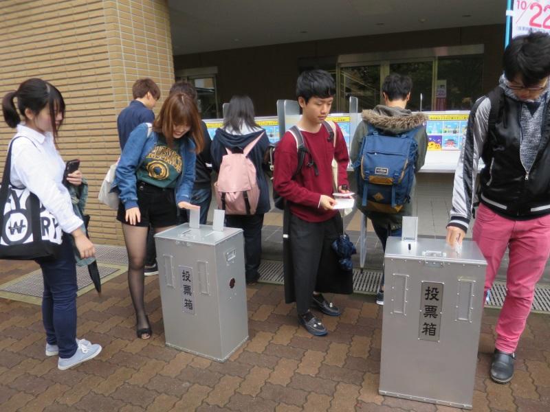 実物の投票箱に一票を投じる学生たち