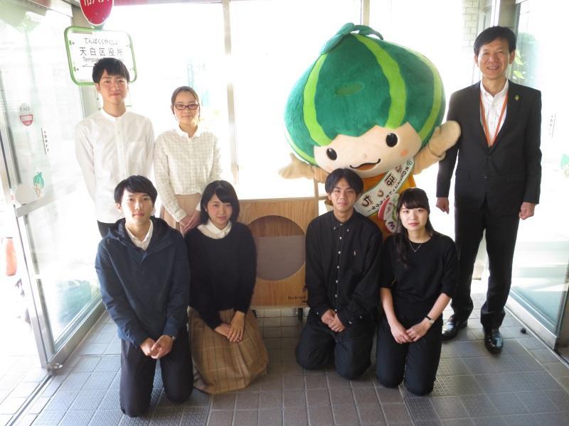 天白区役所玄関に設置された古本回収箱と学生ら(右端は山田区長)