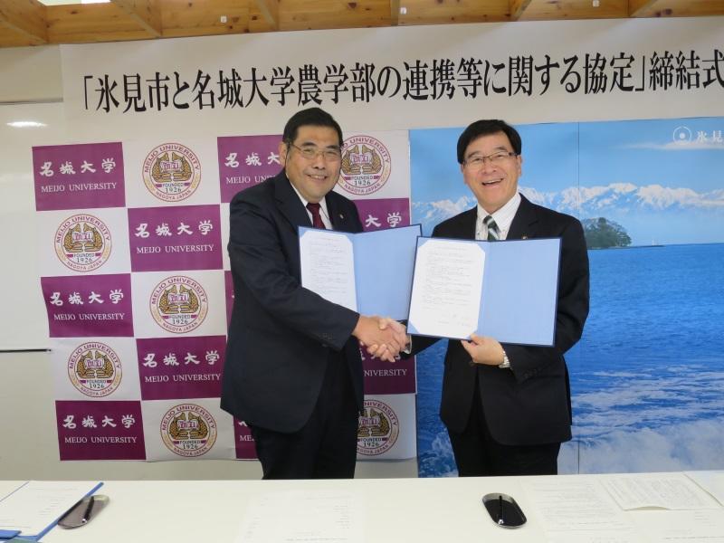 協定を締結し握手する小原学部長(左)と林市長