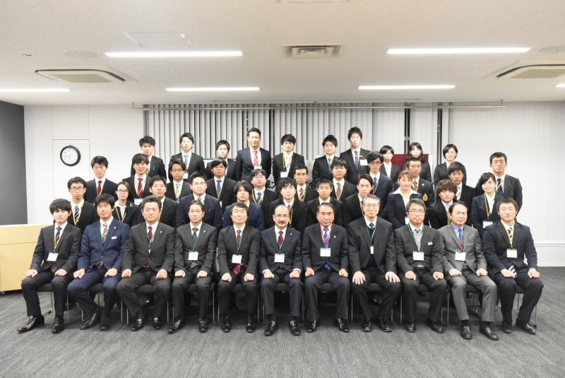集合写真に臨む山田会長(最前列右から5番目)と交付を受けた学生ら