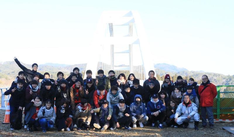 大島と気仙沼市の本土を結ぶ予定の鶴亀大橋の前で記念写真に納まる参加者