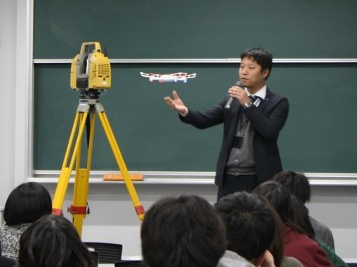 教室内で小型UAVを飛行させデモを行う中山氏