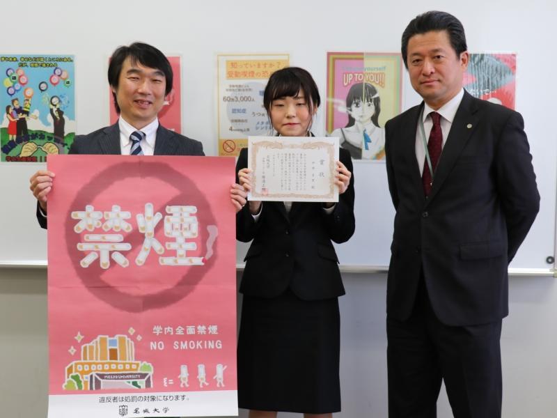 ポスターを手にする勝浦学務センター長と表彰された中井さん(中央)=天白キャンパスのタワー75で