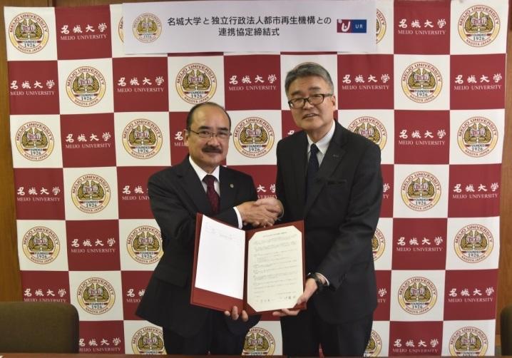 協定を締結し握手する吉久学長(左)と伊藤支社長