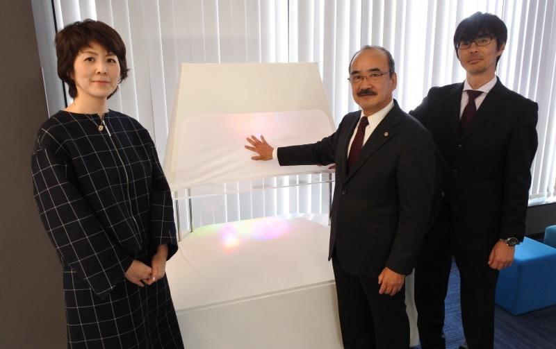 モニュメント「七色の光波」と一緒に写真に納まる吉久学長(中)、生田准教授(左)、竹内教授