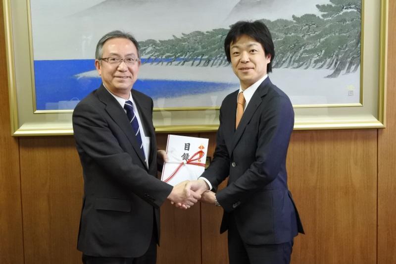 目録を手に握手する加藤常勤理事(左)と林副社長