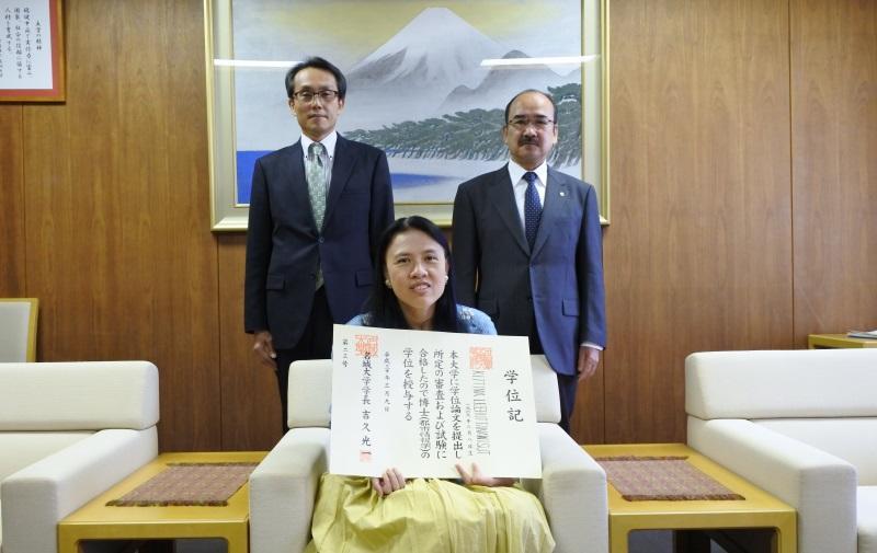 学位記を手にするレルッタナウィストさん(中)と吉久学長(右)、福島教授