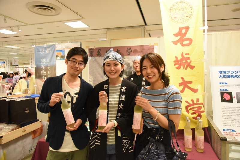 店頭に立った農学研究科農学専攻修士課程1年の糀谷紗季さん(中央)と「華名城」を購入したお客さま