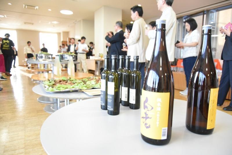 乾杯を前に知多の日本酒と料理の説明を聞く参加者ら