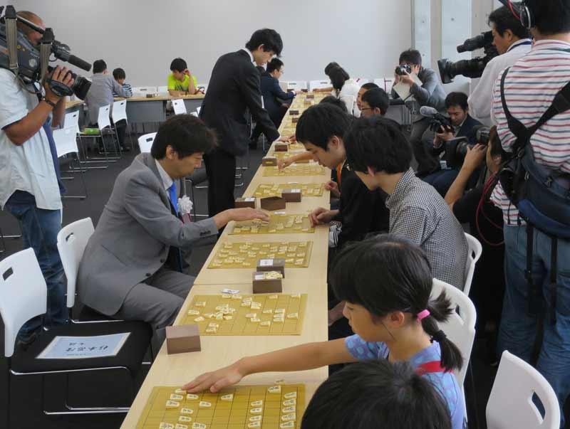 たくさんのテレビカメラの前で指導対局する杉本七段(手前左)らプロ棋士たち
