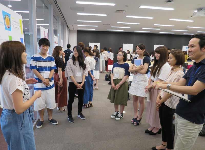 ポスターの前に集まり発表を聞く学生ら
