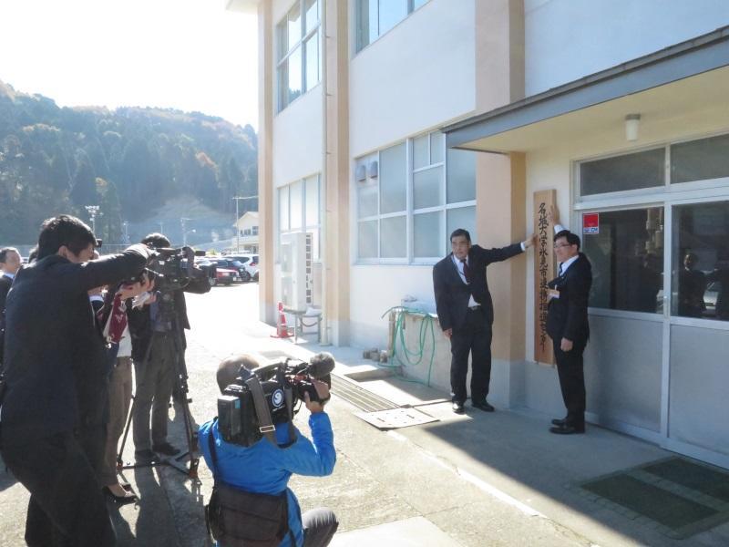 報道陣の前で名城大学氷見市連携推進センターの看板を掛ける小原学部長と林市長