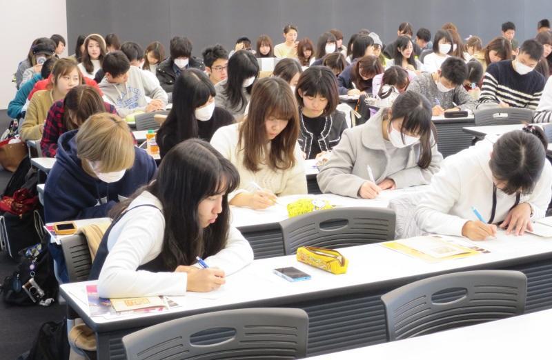 講演を聞いてレポートを書く外国語学部の1年生たち
