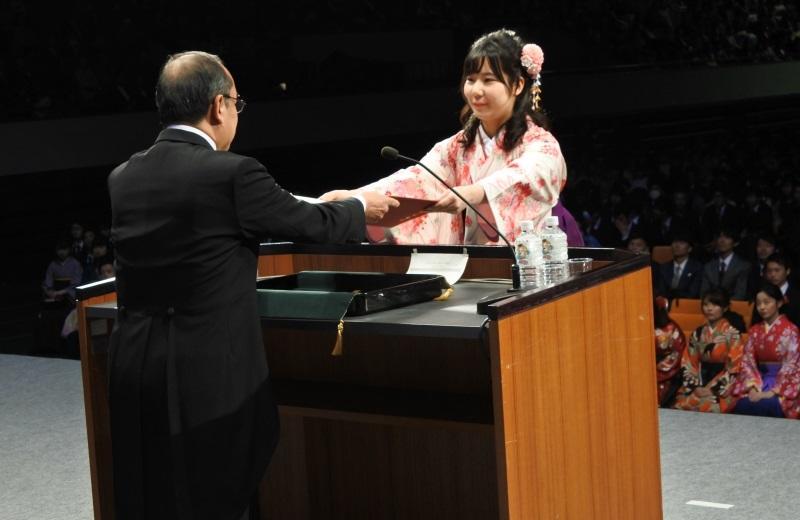 吉久光一学長から学位記を受け取る経営学部経営学科・国際経営学科卒業生代表の間嶋沙紀さん