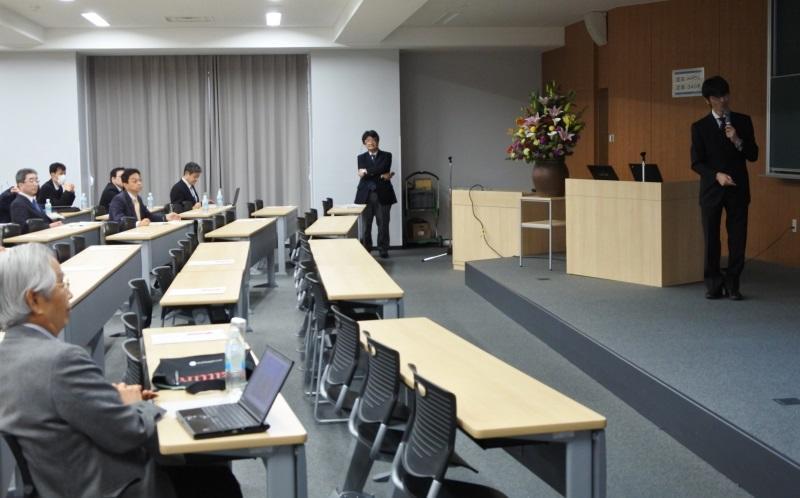 光デバイス研究センター長の竹内教授の発表(右端)と、それを聴く飯島終身教授(左端)