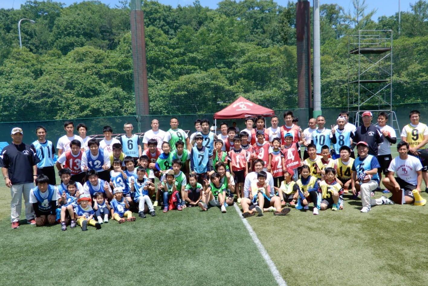アメリカンフットボール部の部員と記念撮影する参加者