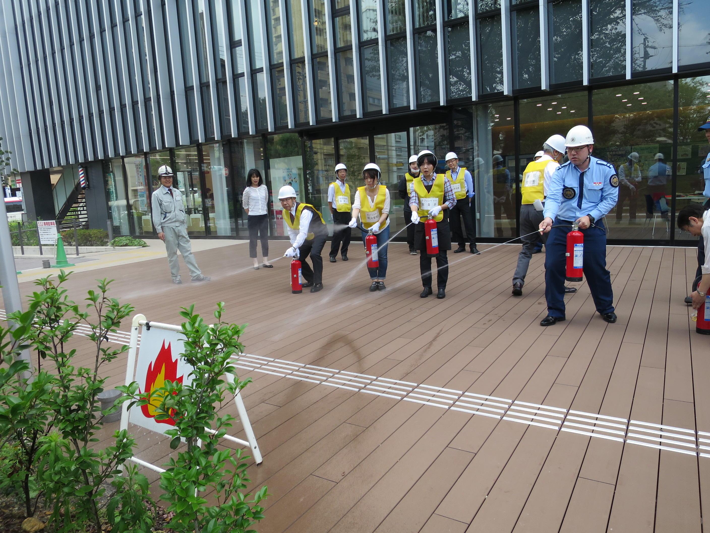 消火器の取り扱い訓練を受ける参加者
