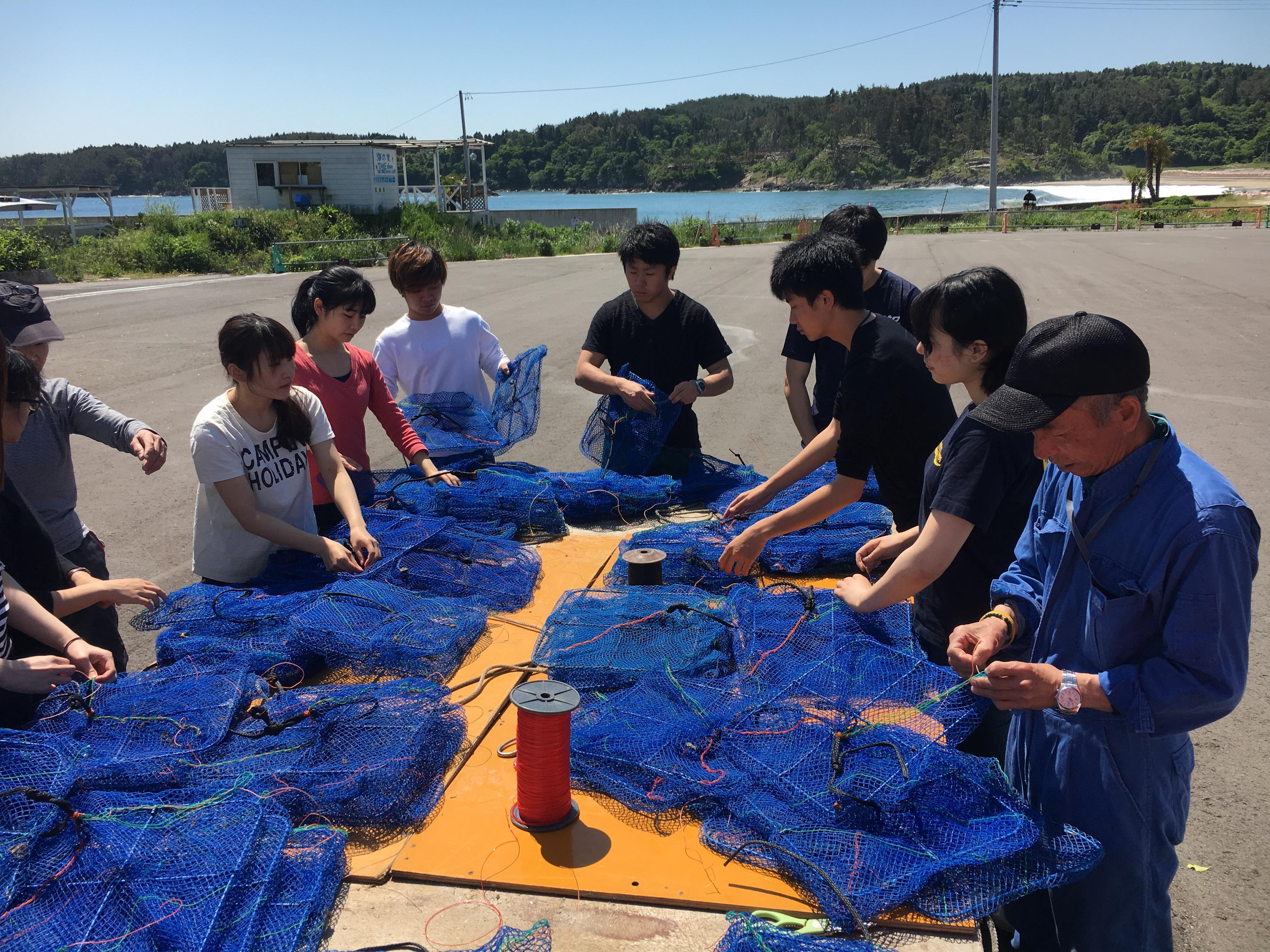 ホタテ貝養殖漁に使用する網の手入れを行う学生ら