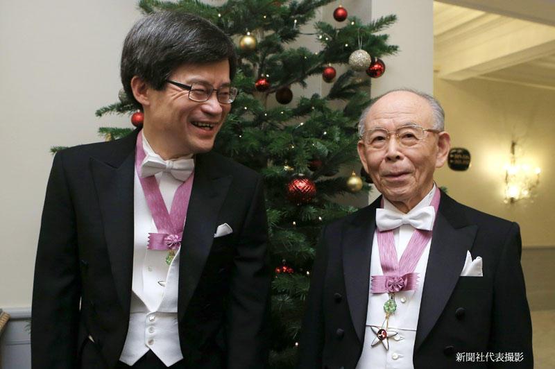 授賞式を前にクリスマスツリーの前で天野教授(左)と記念撮影する赤﨑終身教授=新聞社代表撮影